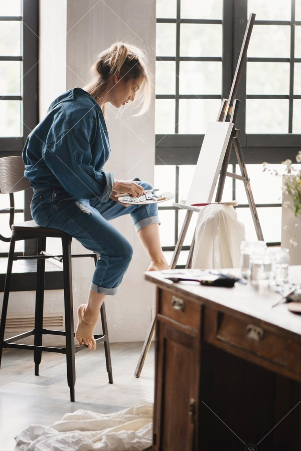 artist painting on easel in studio by window