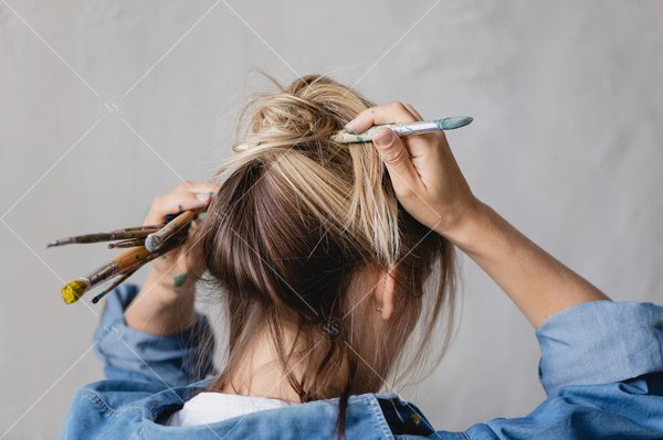 artist putting her hair up with a paintbrush