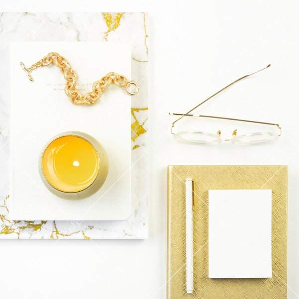 White background styled desktop flatlay stock photo white and gold marble notebook with white journal gold bracelet and gold candle on top next to gold glasses white post its and white pen