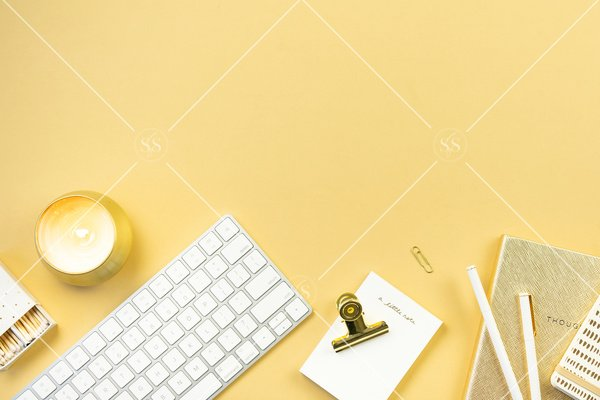 Gold background styled desktop stock photo with white keyboard gold candle gold paperclips gold binder clip white notepad white matches