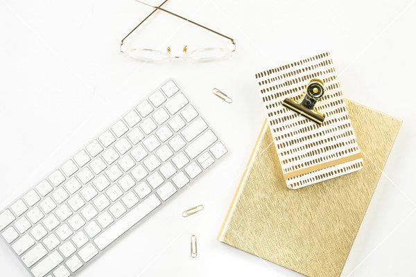 white background flatlay stock photo with white keyboard gold notepad gold journal gold glasses and paperclips