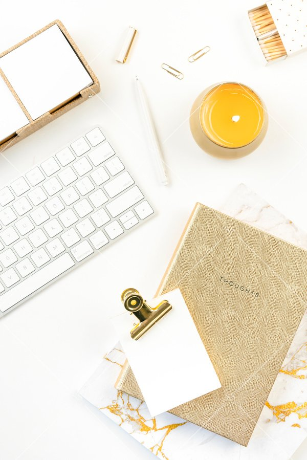 White background flatlay stock photo white keyboard white pen white notepad gold binder clip marble notebook gold journal and gold candle with white matches