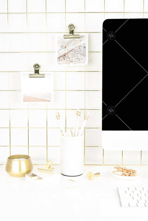 White and gold lifestyle desktop stock photo white imac desktop computer gold grid photo display with 2 square photos on display on desk with white pencils in pencil holder gold candle white notepad white pen white matches gold bracelet and white keyboard