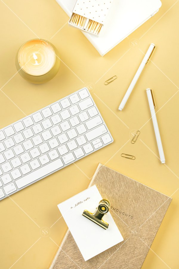 Gold background styled desktop stock photo with white keyboard white book gold candle gold paperclips gold binder clip white notepad white matches gold journal