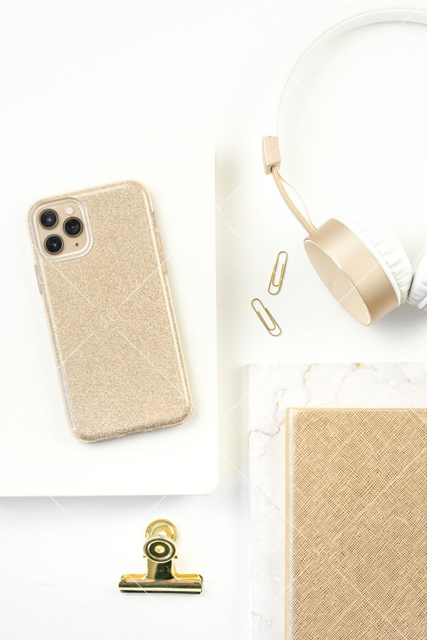 white styled desktop flatlay stock photo with gold iphone white book marble notebook gold journal gold paperclips gold binder clip and white and gold noise canceling headphones