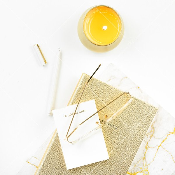 gold candle next to white pen and marble notebook with gold notebook white note pad and gold glass on top styled flatlay stock photo