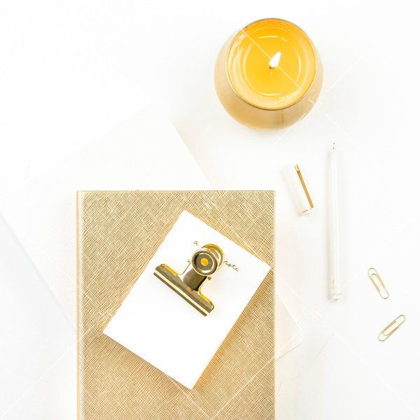 white background with gold candle white notebook gold journal and white notepad with gold binderclip and paperclips flatlay stock photo