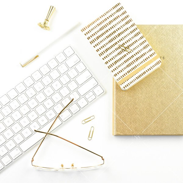 white background flatlay stock photo with white keyboard gold notepad gold journal gold glasses and gold pen and paperclips