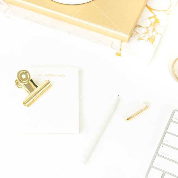 White background flatlay stock photo white keyboard white pen white notepad gold binder clip marble notebook and gold journal
