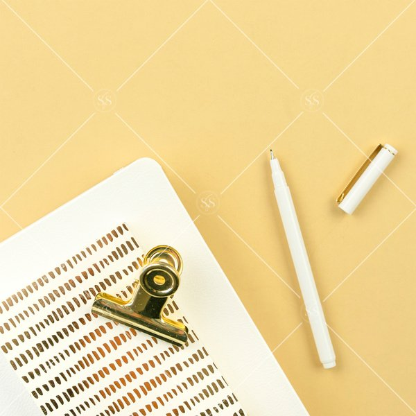 Gold background flatlay stock photo with white notebook white and gold notepad and white and gold pen