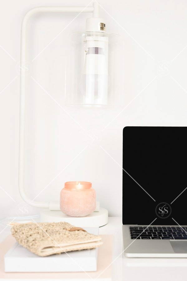 laptop on a desk with a lamp and candle