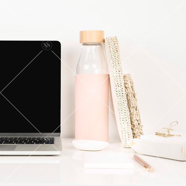 laptop with reusable waterbottle and notebooks on a desk