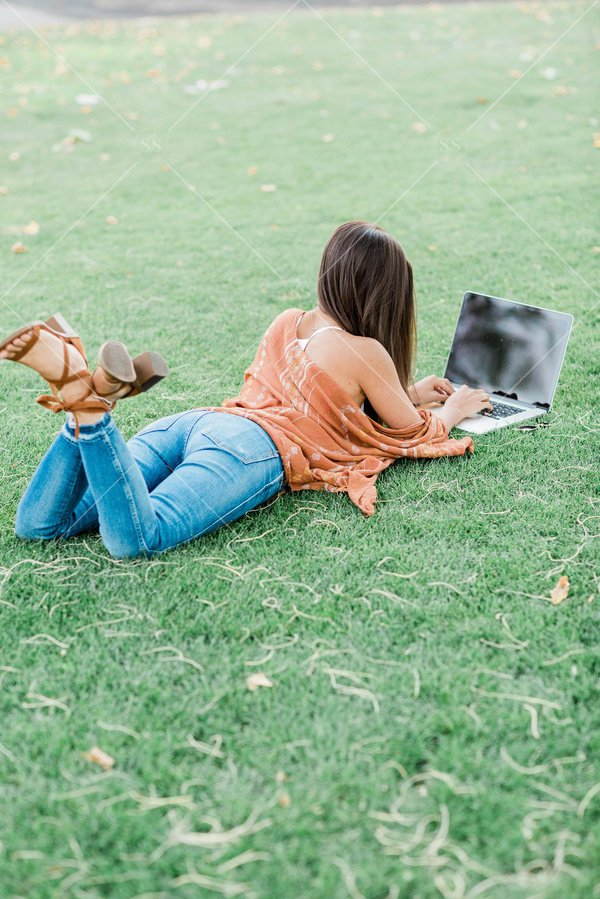 woman working on a laptop laying in the grass