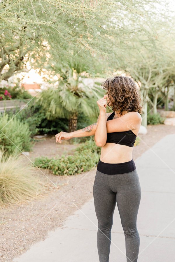 Woman stretching outside in workout clothing
