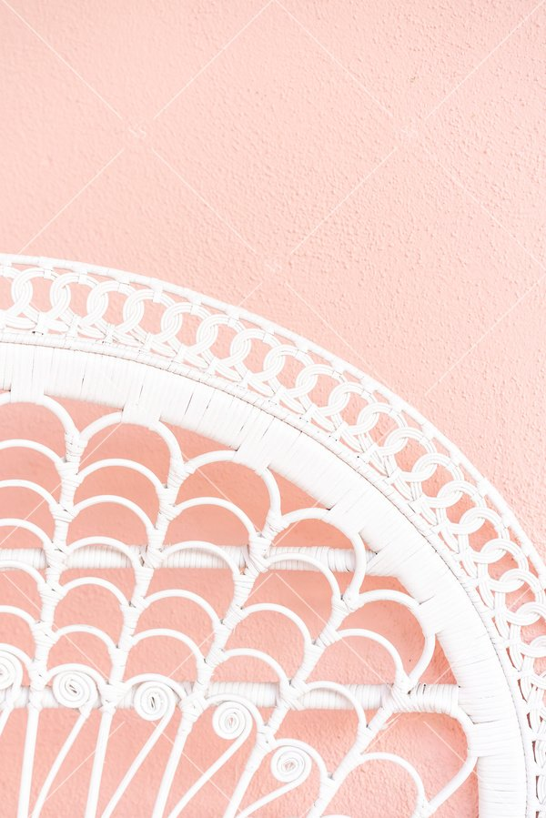 white woven chair pink wall