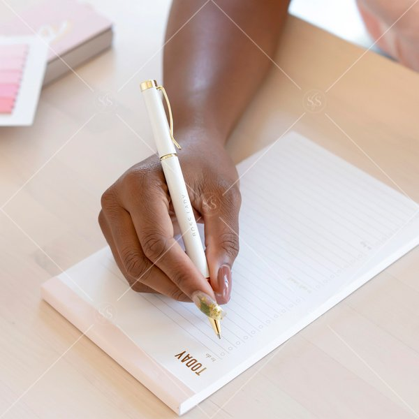 woman of color writing on a to do list