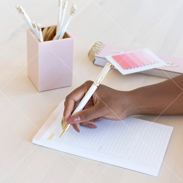 woman of color writing on a pad of paper