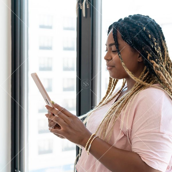 woman of color reading on tablet