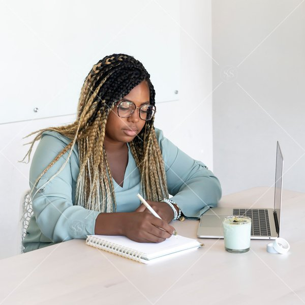 woman of color writing in a notebook with laptop and candle