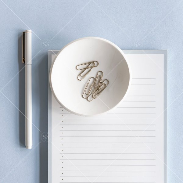 work flat lay with list pad, pen, and paperclips in a cup