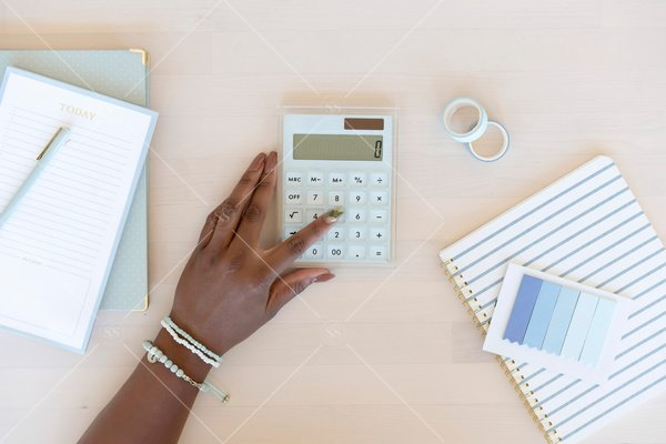 woman of color using analogue calculator on a desk