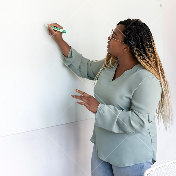 woman of color writing on a whiteboard
