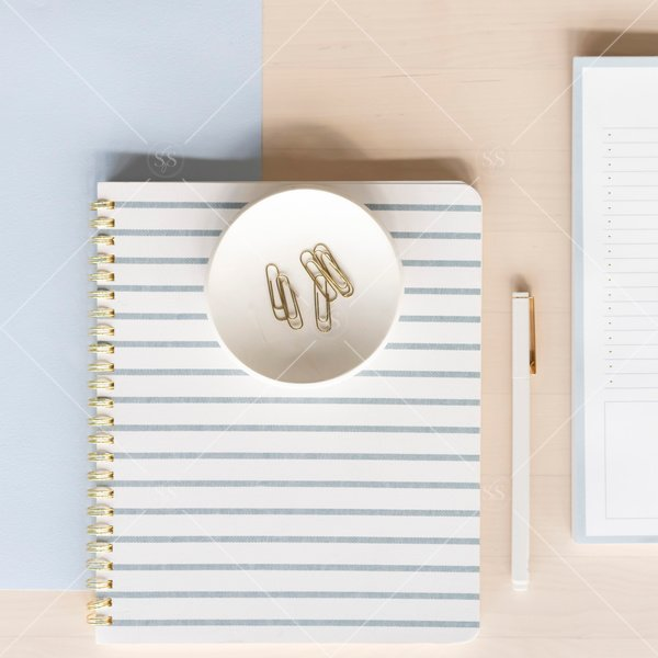 desk flat lay with notebooks, a pen and paperclips