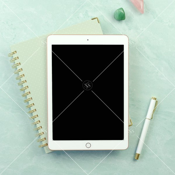 iPad and notebook on a seafoam green background