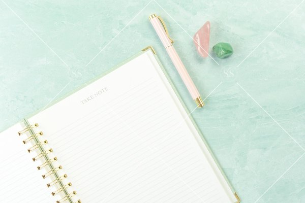 notebook with pen and crystals on seafoam green background