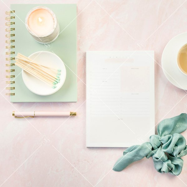 candle, notebooks, and scrunchie on a pink background