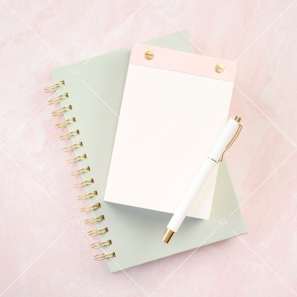 pink notepad and green notebook